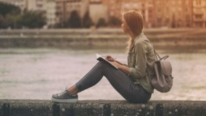 Woman writing prayer request into journal