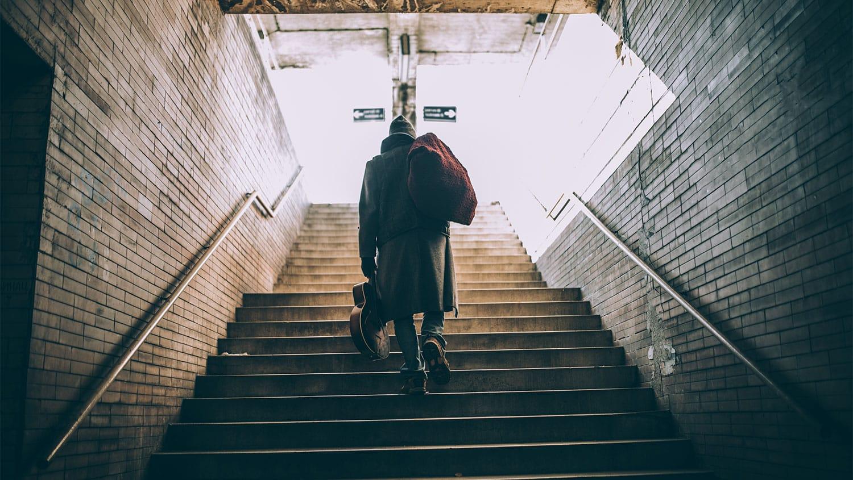 Homeless man walking up stairs