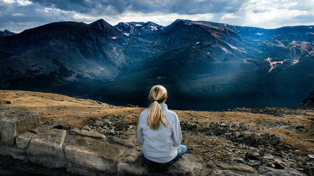 person sitting looking at mountains
